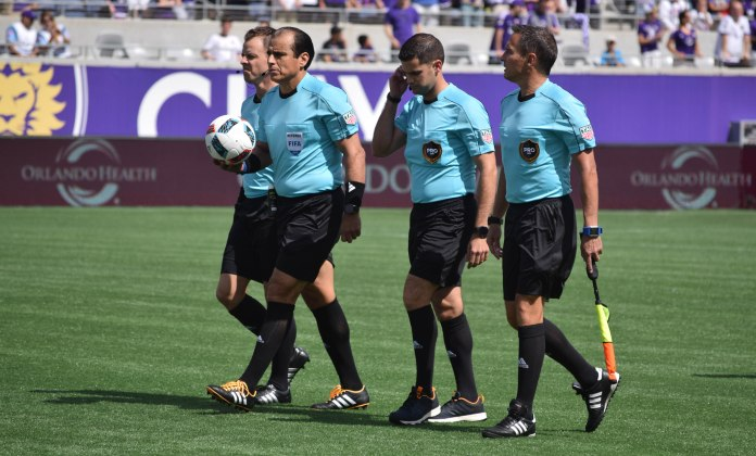 The referees, led by Baldomero Toledo (with ball), walk onto the field prior to a match between the Orlando City Lions and the New England Revolution in the Orlando Citrus Bowl on Sunday, April 17, 2016. The referees were at the center of late-game drama surrounding a controversial call. (Victor Ng / Orlando Soccer Journal)